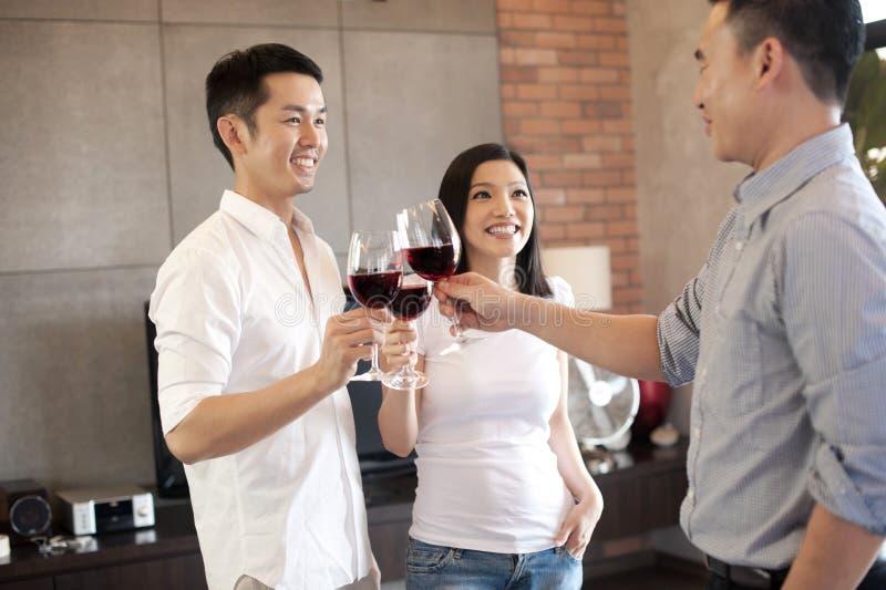 Aziatische familie met vriend met een glasofwine stock afbeelding