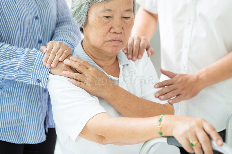 Aziatische familie troostende gedeprimeerde hogere vrouw; de droevige bejaarde mensen met depressieve symptomen hebben dichte zor stock fotografie