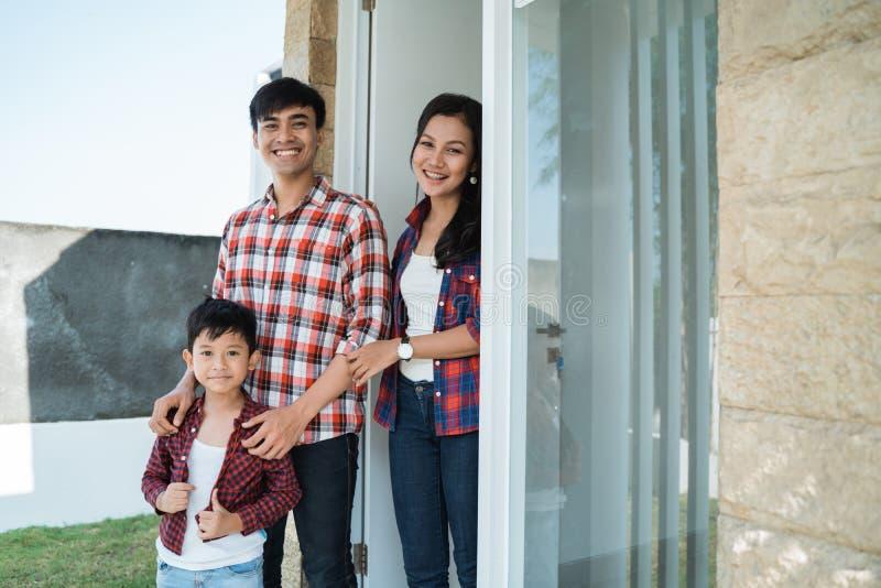 Aziatische familie voor de deur van hun huis stock fotografie