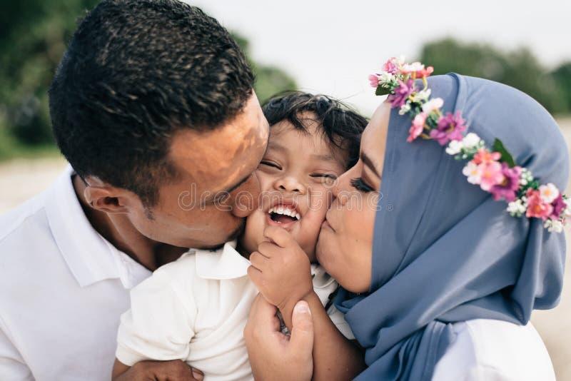 Aziatische familiemoeder en vader die hun zoon kussen stock afbeeldingen