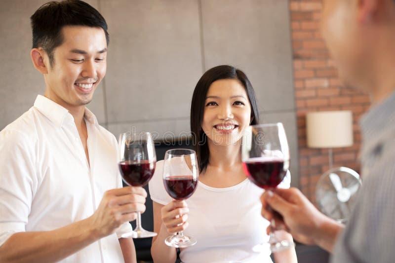 Aziatische familievriend die zich met wijn bevindt royalty-vrije stock afbeeldingen