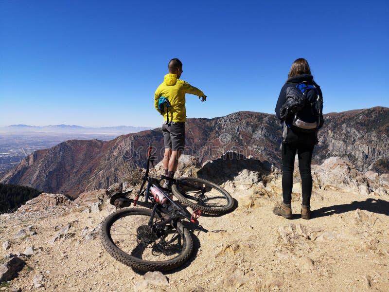 Aziatische fietser die wijst en een kaukasische wandelaar die geniet van het uitzicht van Sardine Peak Trailhead stock foto's