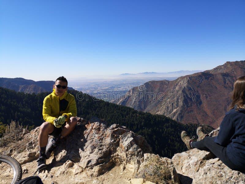 Aziatische fietser zit te rusten en kijkt naar camera terwijl een kaukasische wandelaar geniet van het uitzicht van Sardine Peak  stock foto's