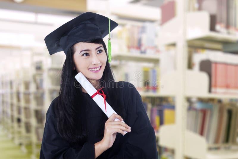 Aziatische gediplomeerde dragende graduatietoga bij bibliotheek stock fotografie