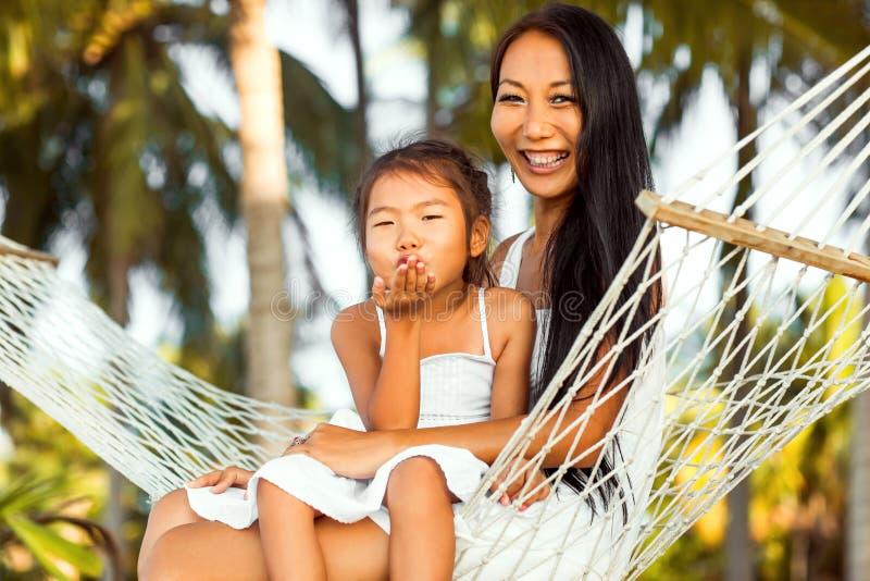 Aziatische gelukkige moeder met haar dochterzitting in een hangmat op stock afbeelding