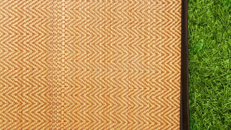 Aziatische geweven hout of rotanmat op de groene achtergrond van de grastextuur royalty-vrije stock afbeeldingen