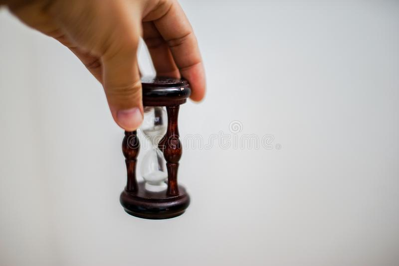 Aziatische Hand die een zandloper op witte achtergrond houden stock afbeeldingen