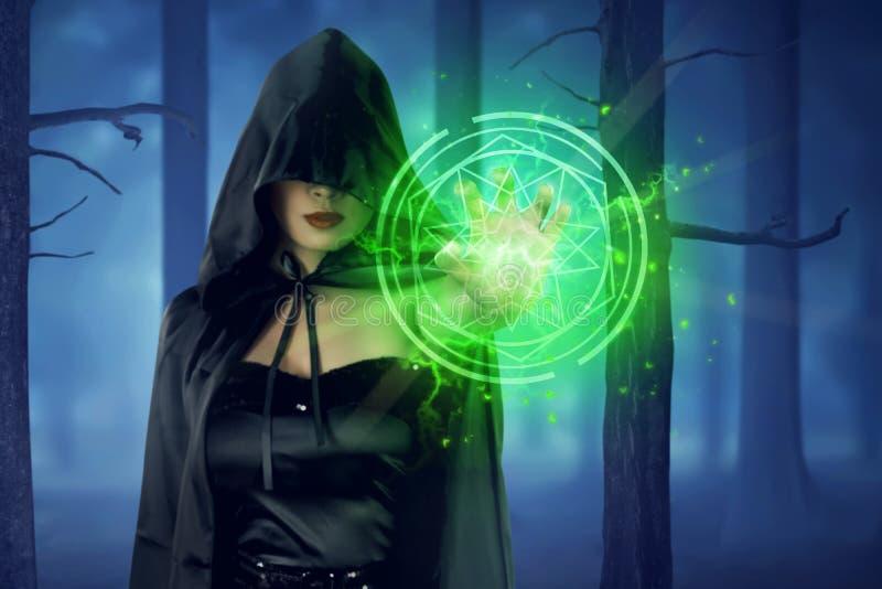 Aziatische heksenvrouw met mantel die groene pentagram tonen royalty-vrije stock afbeelding
