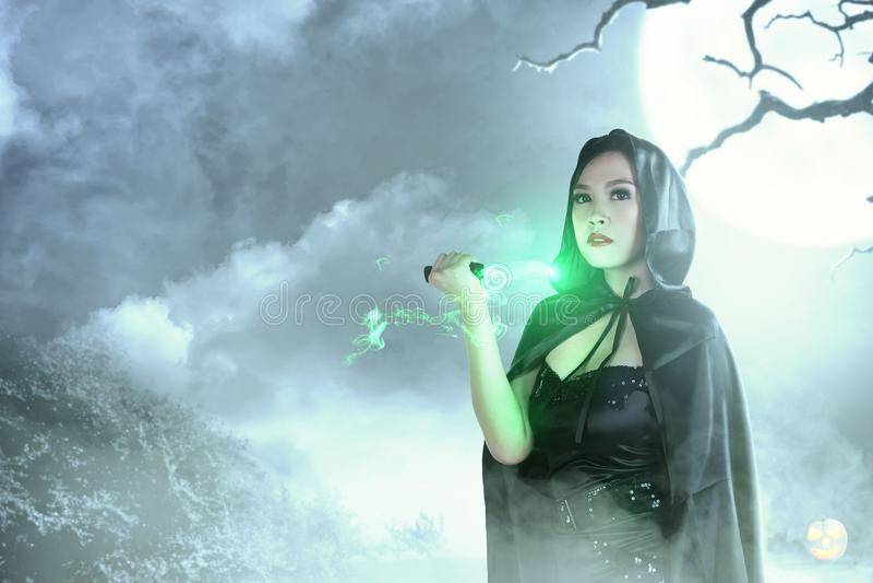 Aziatische heksenvrouw in zwarte het doen rituele magisch met een kap met een mes stock fotografie