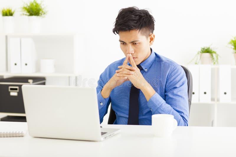 Aziatische het bedrijfsmens letten op laptop en het denken royalty-vrije stock foto