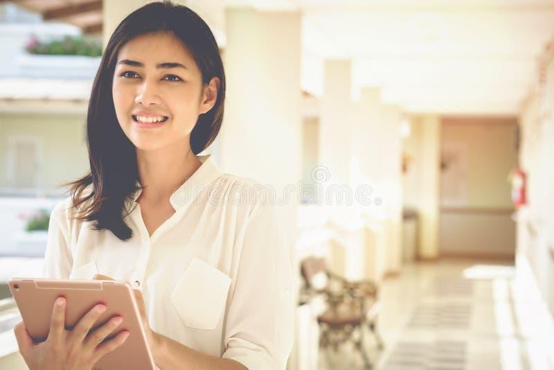 Aziatische het gebruikstablet van vrouwenzakenlieden om het werk en zaken te contacteren stock foto's