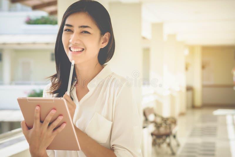 Aziatische het gebruikstablet van vrouwenzakenlieden om het werk en zaken te contacteren royalty-vrije stock afbeelding