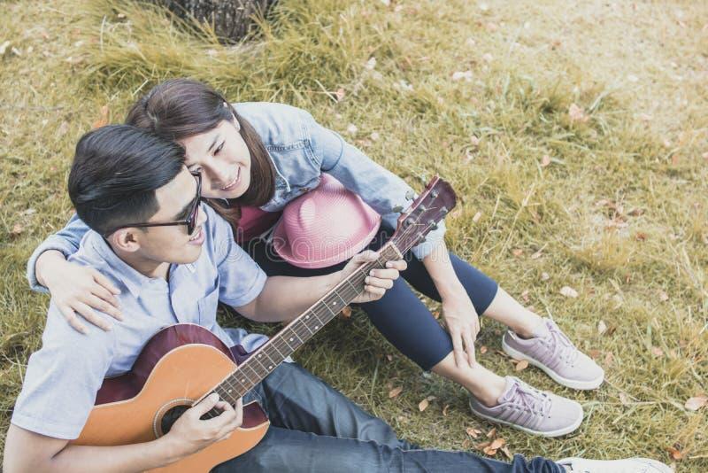 Aziatische het spelgitaar van het minnaarpaar in park, romantisch en valentijnskaart D stock foto's