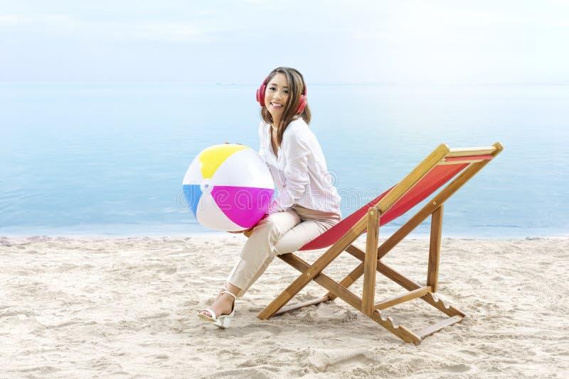 Aziatische het strandbal van de bedrijfsvrouwenholding terwijl het gebruiken van hoofdtelefoons die in de ligstoel op strand zitt stock afbeelding