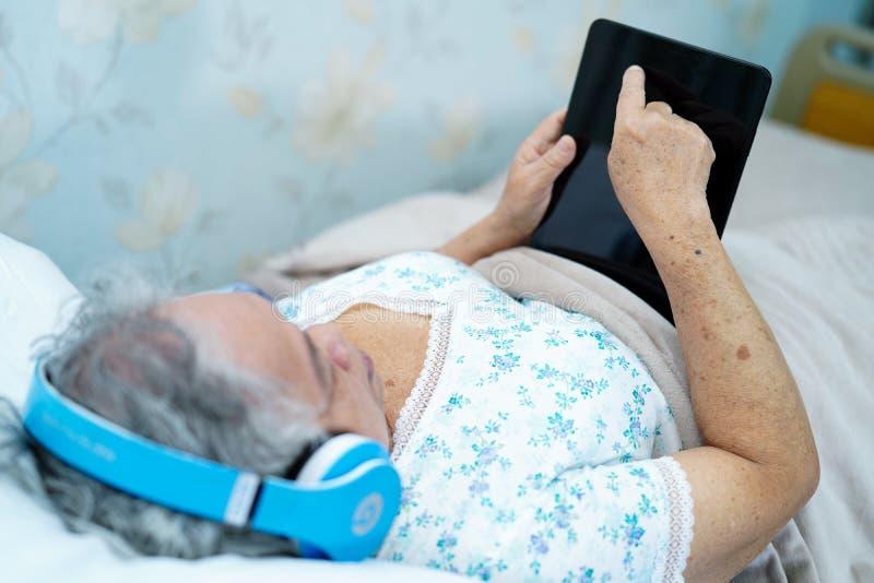 Aziatische hogere of bejaarde oude geduldige het gebruiksoortelefoon van de damevrouw terwijl en gelukkig op bed in de verzorging stock foto