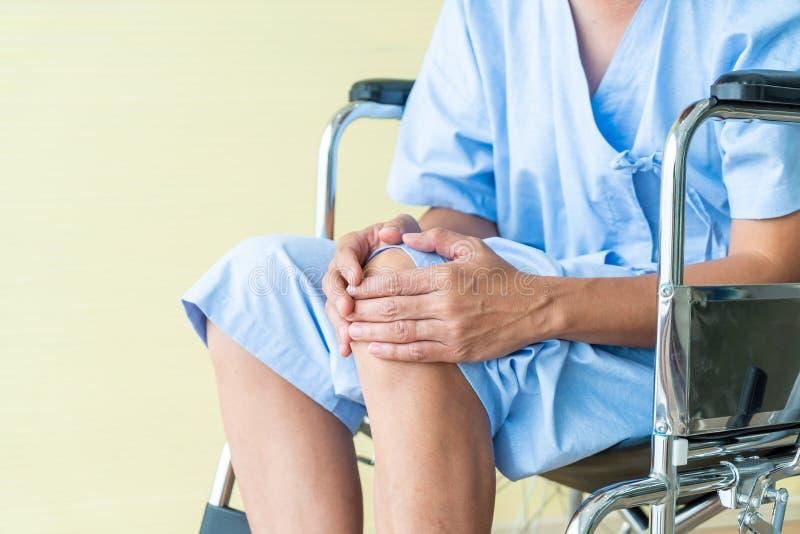 Aziatische hogere geduldige rolstoel met kniepijn stock foto's