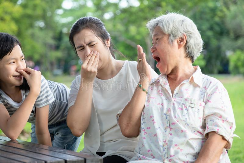 Aziatische hogere grootmoeder die adem met haar hand controleren, bejaarde mensenslechte adem die, dochter, kleindochter haar zee stock afbeeldingen