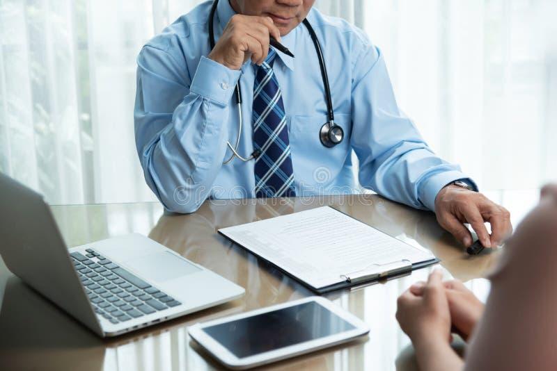 Aziatische Hogere Mannelijke arts die in blauw overhemd iets denken stock foto