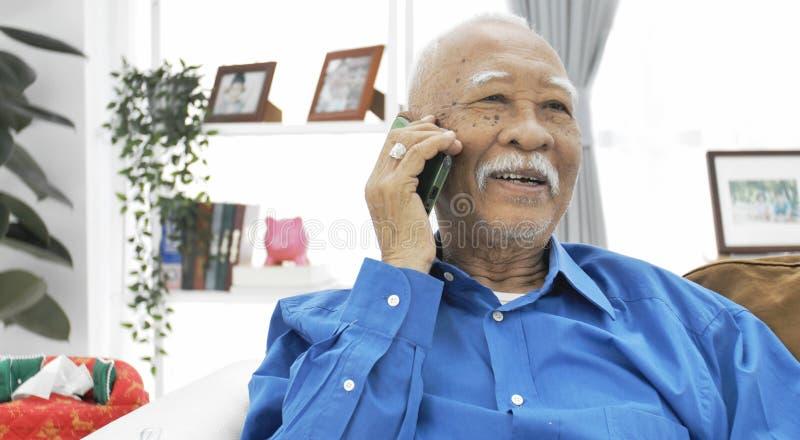 Aziatische Hogere mens met witte snor die met smartphone spreekt stock afbeelding