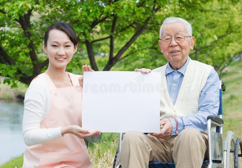 Aziatische hogere mensenzitting op een rolstoel met verzorger en witte raad royalty-vrije stock foto