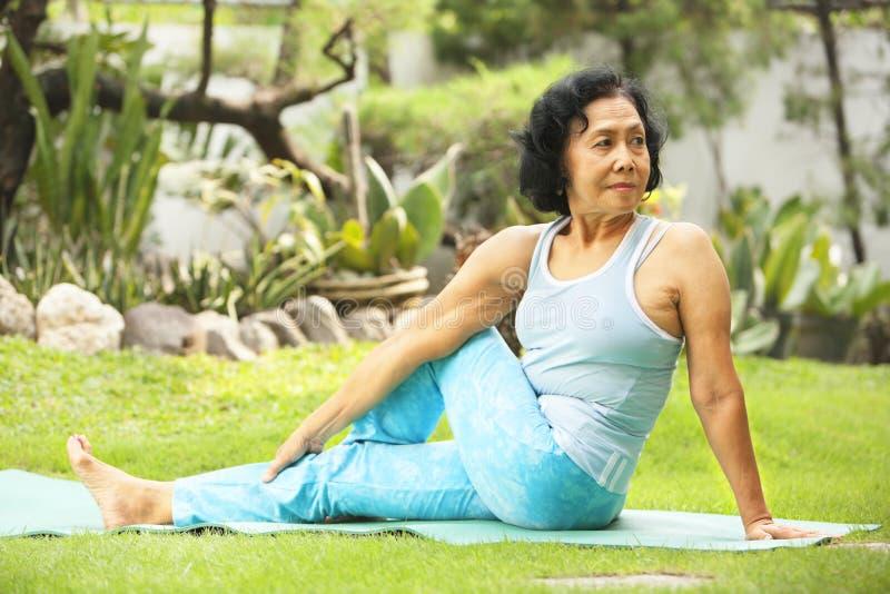 Aziatische hogere oude vrouw die yoga doet royalty-vrije stock fotografie