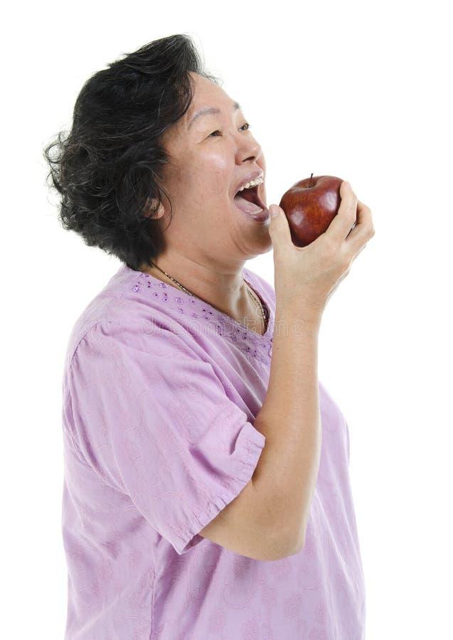 Aziatische Hogere volwassen vrouw die appel eten stock foto
