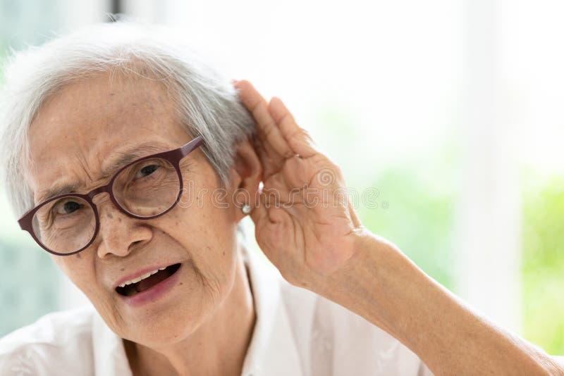 Aziatische hogere vrouw die door hand's tot het oor luisteren, die moeilijkheid in hoorzitting, bejaarde hebben moeilijk te hor stock foto's