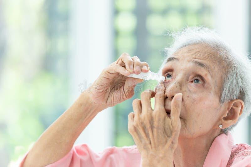 Aziatische hogere vrouw die oogdaling, close-upmening zetten van bejaarde persoon die fles eyedrops in haar ogen met behulp van,  stock foto's