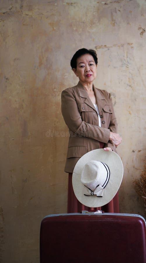 Aziatische hogere vrouwen uitstekende hoed, retro manier met reis luggag stock foto