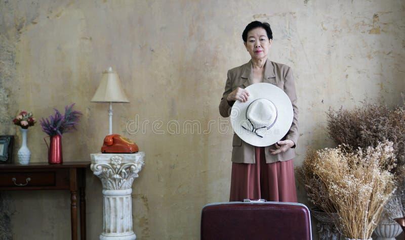 Aziatische hogere vrouwen uitstekende hoed, retro manier met reis luggag royalty-vrije stock foto's