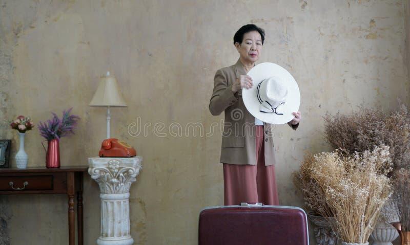 Aziatische hogere vrouwen uitstekende hoed, retro manier met reis luggag stock foto's