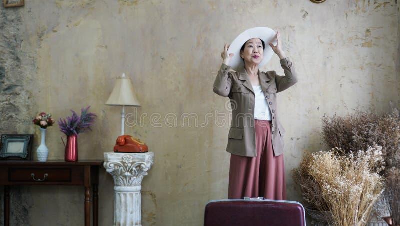 Aziatische hogere vrouwen uitstekende hoed, retro manier met reis luggag royalty-vrije stock afbeeldingen