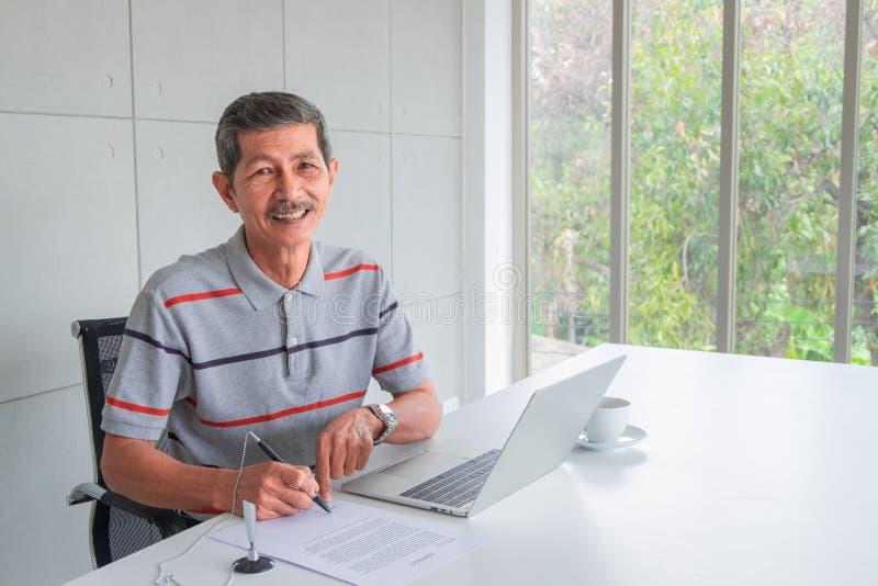 Aziatische Hogere zakenman, het Glimlachen Gebruiken een Pen voor teken stock afbeelding