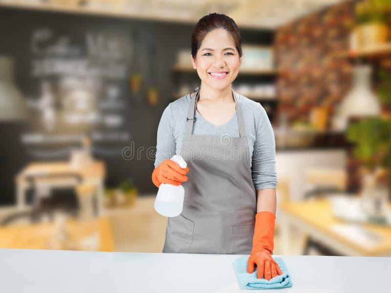 Aziatische huisvrouw die op lijst vegen royalty-vrije stock foto's