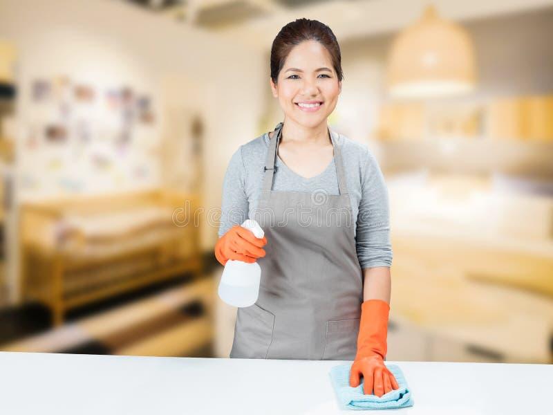 Aziatische huisvrouw die op lijst vegen royalty-vrije stock afbeelding