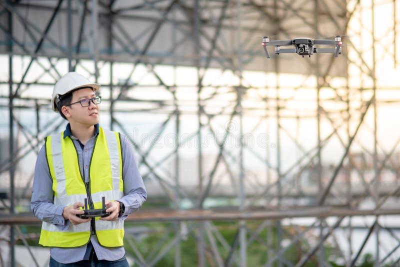 Aziatische ingenieurs vliegende hommel over bouwwerf royalty-vrije stock afbeeldingen