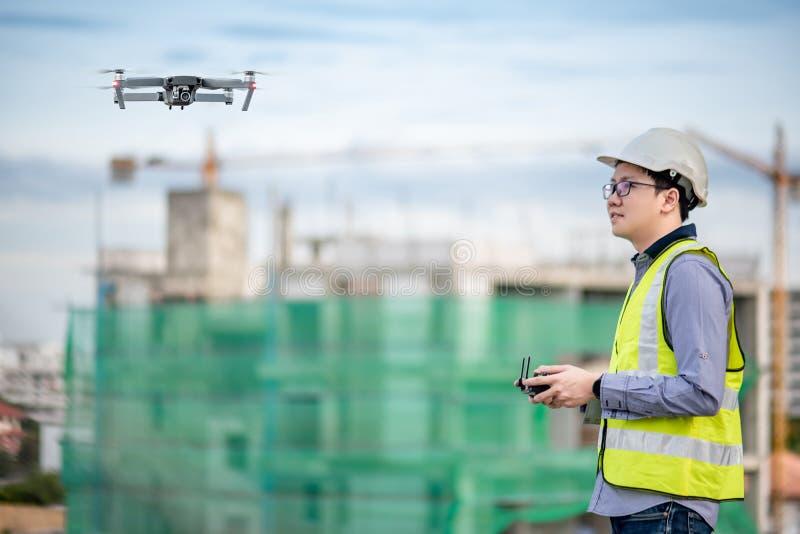 Aziatische ingenieurs vliegende hommel over bouwwerf stock fotografie