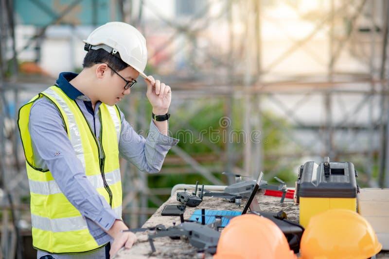 Aziatische ingenieursmens die hommel voor plaatsonderzoek gebruiken stock foto
