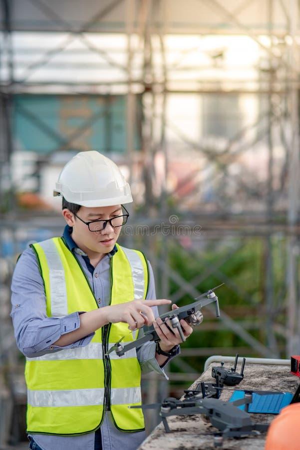 Aziatische ingenieursmens die hommel voor plaatsonderzoek gebruiken stock afbeeldingen