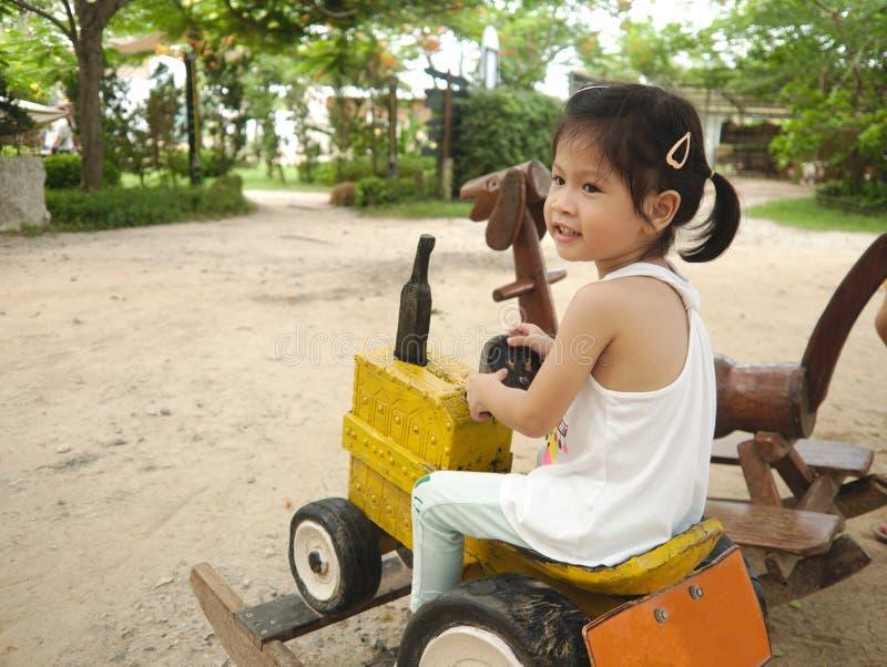 Aziatische jong geitjezitting op houten autostuk speelgoed terwijl het spelen in speelplaats met gelukkig glimlachgezicht die aan royalty-vrije stock afbeeldingen