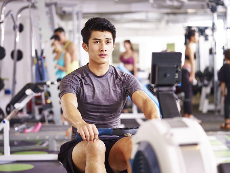 Aziatische jonge mens die op het roeien machine uitwerken stock afbeeldingen