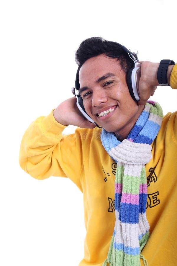 Aziatische jonge mens het luisteren muziek stock foto's