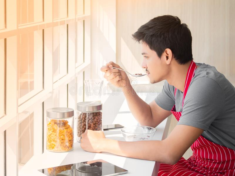 Aziatische jonge mensenzitting naast glazen venster en het hebben van graangewas met melk op lijst voor ontbijt thuis in de ochte royalty-vrije stock foto