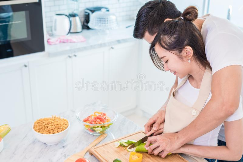 Aziatische jonge minnaars of paren die ontbijt in de ochtend in keukenruimte koken Man het onderwijsvrouw aan plakgroente en rijs stock foto