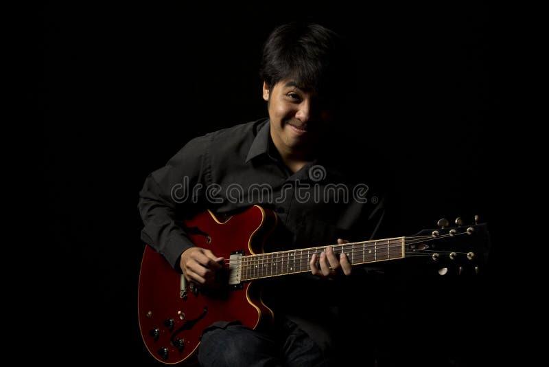 Aziatische jonge musicus het spelen gitaar royalty-vrije stock foto's
