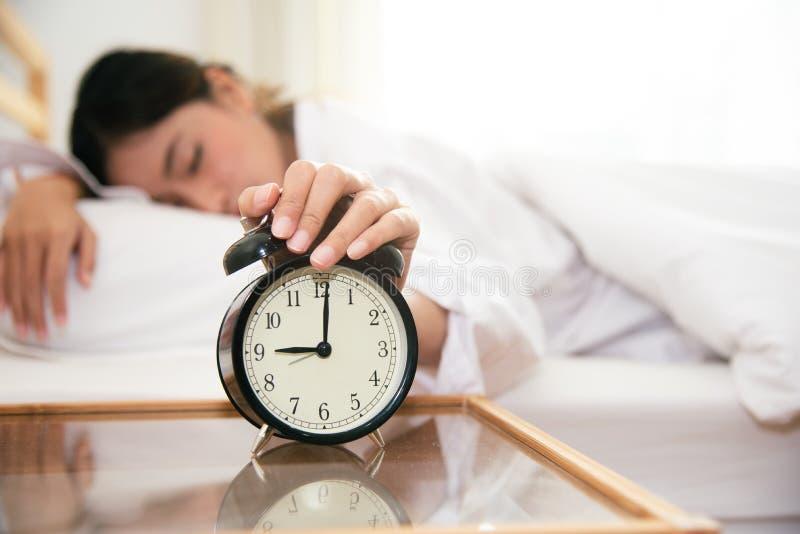 Aziatische jonge schoonheidsvrouw die wekker in ochtend laat zonder het kijken uitzetten klok en lui aan het werken aan in vakant stock fotografie
