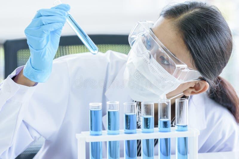 Aziatische jonge studentenwetenschapper die en in een laboratorium onderzoeken leren stock afbeelding