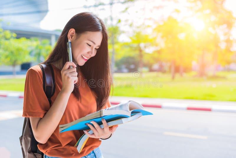 Aziatische jonge universiteitsvrouw die thuiswerk doen en boeken voor F lezen royalty-vrije stock fotografie