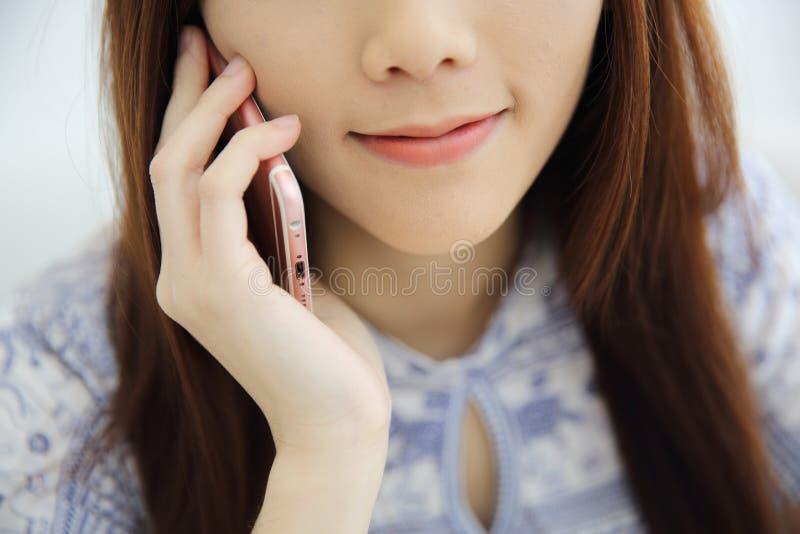 Aziatische jonge vrouw die het spreken op telefoon callephohe in coffeeshop roepen royalty-vrije stock fotografie