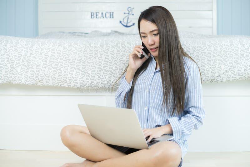 Aziatische jonge vrouw die laptop computer en smartphone in haar slaapkamer gebruiken Thuis het werken van concept royalty-vrije stock afbeelding